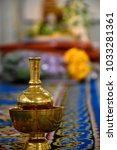 Small photo of A golden container or pedestal in a cup used for storing water to be poured as dedication to make a libation while listening to sermon and receiving precepts from Buddhist monks as per Buddhism belief
