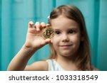 little girl holding a bitcoin...   Shutterstock . vector #1033318549