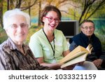 nurse reading book to elderly... | Shutterstock . vector #1033321159