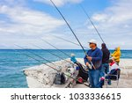 Small photo of Cape Town, South Africa, September 22, 2013, People fishing with rod and reel off a harbor wall