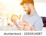 proud father carries his... | Shutterstock . vector #1033414087