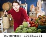 teenager takes an artichoke in... | Shutterstock . vector #1033511131