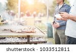 man cooking meat at dinner... | Shutterstock . vector #1033512811