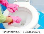 a woman cleans a bathroom... | Shutterstock . vector #1033610671