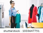 Small photo of Portrait of stylish fashion consultant of famous designer with tape for measures holding hanger with trendy blue dress standing near black mannequin with textile material while looking at camera