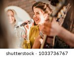 Entertianment at a wedding. A female singer is interacting with the crowd while a man plays an acoustic guitar.  - stock photo