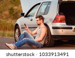a young man sits on the asphalt ... | Shutterstock . vector #1033913491