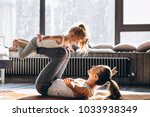 mother and daughter yoga at home | Shutterstock . vector #1033938349