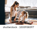 mother and daughter yoga at home | Shutterstock . vector #1033938397
