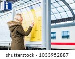 woman reading time table in... | Shutterstock . vector #1033952887