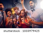 group of friends dancing at the ... | Shutterstock . vector #1033979425