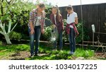 teenage girls watering garden...   Shutterstock . vector #1034017225