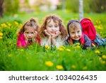 three children lie on the green ... | Shutterstock . vector #1034026435