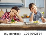 Small photo of We hate vegetables. Attractive sad dark-haired little brother and sister sitting at the table and having healthy breakfast and looking sadly at the vegetables