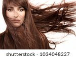 Small photo of Hair care and beauty concept. Beautiful model girl wearing subtle makeup with gorgeous healthy long hair blowing to the side in a breeze. Beauty portrait isolated on white in a close up cropped view