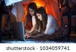 smiling girls in pajamas using... | Shutterstock . vector #1034059741