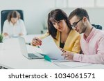 colleagues working at office in ... | Shutterstock . vector #1034061571