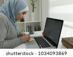 young muslim girl wotking on... | Shutterstock . vector #1034093869