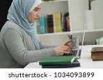 young muslim girl wotking on... | Shutterstock . vector #1034093899