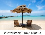beach chairs and umbrella on... | Shutterstock . vector #1034130535