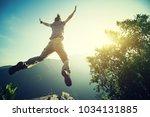 hipster woman hiker jumping on... | Shutterstock . vector #1034131885