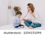 happy family   mother playing... | Shutterstock . vector #1034151094