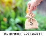 female hand holding a sack of... | Shutterstock . vector #1034163964