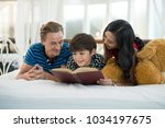 dad and mom looking at my son... | Shutterstock . vector #1034197675