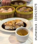 Small photo of Dim sum, a Chinese food that consists of variety of stream food (pork shumai and shimp har gao) and a cup of tea.