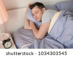 young man sleeping in bed at...   Shutterstock . vector #1034303545