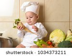 adorable baby boy in kitchen | Shutterstock . vector #1034373211