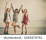 three fashionable women having... | Shutterstock . vector #1034374741