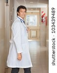 Portrait of a happy doctor at hospital corridor - stock photo