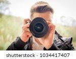 young blonde man shooting photos | Shutterstock . vector #1034417407
