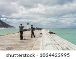 Small photo of Cape Town, South Africa, September 28, 2013, Teenagers fishing with rod and reel off a harbor wall