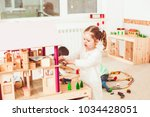 girl playing with a dollhouse | Shutterstock . vector #1034428051