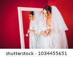 bride looks at herself in the... | Shutterstock . vector #1034455651