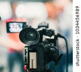 camera at media conference | Shutterstock . vector #1034456989