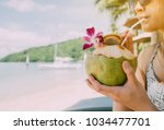 close up woman drink a coconut... | Shutterstock . vector #1034477701