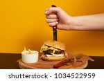 hand stabbing with knife burger ...   Shutterstock . vector #1034522959