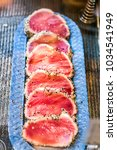 Small photo of Seared raw ahi tuna rare steaks with black pepper crust on display in market, restaurant, shop, deli counter, sesame seeds