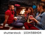 friend's relaxation after skiing in front of fireplace at home - stock photo