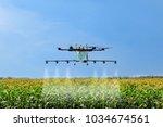 drone spray pesticide in corn... | Shutterstock . vector #1034674561