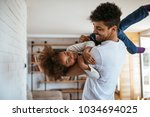 father playing with his... | Shutterstock . vector #1034694025