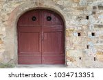 arched red door in medieval... | Shutterstock . vector #1034713351