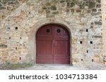arched red door in medieval... | Shutterstock . vector #1034713384