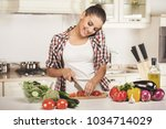 young woman is chopping... | Shutterstock . vector #1034714029