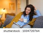 Brunette Woman Sitting On Sofa  ...
