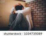 depressed man sitting head in... | Shutterstock . vector #1034735089