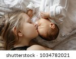 blonde little girl and 1 month... | Shutterstock . vector #1034782021